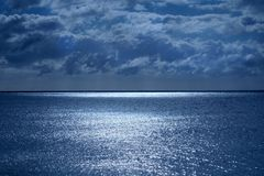 Sea and sky in the bottom half is a calm deep blue sea, on the horizon is a line of white shimmering glowing light from the moon royalty free stock image