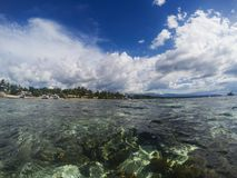 Sea and sky double landscape. Tropical seascape split photo. Double seaview. Underwater coral reef. Above and below waterline border. Exotic seashore. Coral Stock Photos