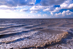 Sea sky storm. Landscape of the Sea of Azov by a windy summer evening. Waves on the water surface, blue sky with clouds Stock Image