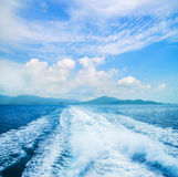 Sea, sky and a trace on the water Stock Image