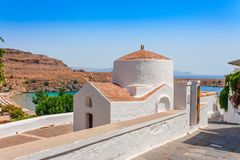 Sea skyview landscape photo bay and orthodox church in Lindos on Rhodes island, Dodecanese, Greece. Panorama with nice sand beach. And clear blue water. Famous royalty free stock photo