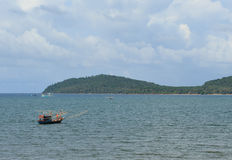 Sea and small fishing boat stock images