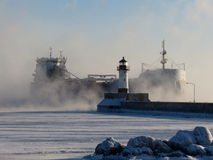 Sea Smoke Arrival. A Canadian freighter enters the Duluth harbor on Lake Superior on a cold winter day in January as the waters steams and let's off heat in the Royalty Free Stock Images