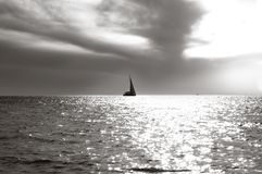 Lonely sailing vessel on horizon and a sea smooth surface in beams of sun