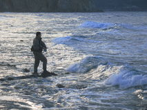 Sea soinning. A fisherman fishing with lures in the coast of Sardinia Stock Image