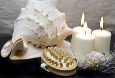 Sea spa. Some sea elements with massage brush and lit candles, black background Royalty Free Stock Photos