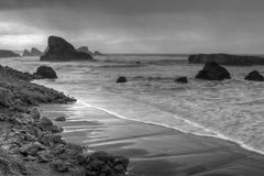 Sea Spires along Oregon Coast. Wide view of Sea Spires in Southern Oregon with waves washing in against shoreline in Black and White Stock Photography