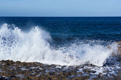 Sea splashing on rocks Stock Images