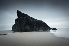 Sea stack on a beach in Cornwall. Stock Images