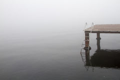 Sea, stairs, pier and foggy day. A wooden pier and stairs to sea in a foggy day royalty free stock photography