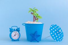 Starfish, paper cocktail parasol, can with sand and plastic palm tree isolated on blue background. Summertime vacation minimalisti royalty free stock photography
