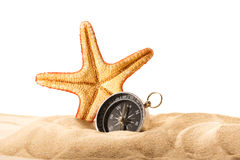 Sea star and compass in sand Royalty Free Stock Photo