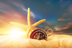 Sea star and compass in sand on sunset Stock Photos