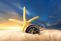 Sea star and compass in sand on sunset Royalty Free Stock Photo