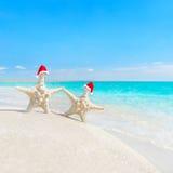 Sea-stars couple in santa hats at sea beach. New Years or Christ Stock Photos
