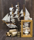 Sea still life with hourglass, scrolls and ship Royalty Free Stock Photography