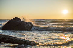 Sea. Stone breaking waves at sunset Stock Photos