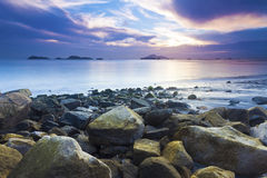 Sea stones along coast at sunset Royalty Free Stock Photos