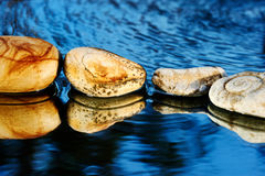 Sea stones on dark blue. Four stones on dark blue background in water Stock Image
