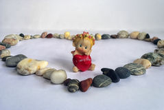Sea stones laid out in the heart and an angel figurine. On a white background a symbol of the heart is laid out of the stones, and in it is an angel figure with stock photography