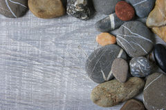 Sea stones lie on the board Stock Photography