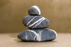 Sea stones pebbles pyramid. On a wooden background royalty free stock image