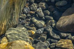 Sea stones and rocks of different sizes and texsture of black, gray and brown under the water on the Black Sea. Coast as nature bacground. Excellent concept for stock photography