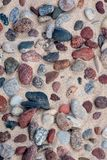 Sea stones of various sizes and colors. Small stones in the sand of the seashore; sea stones of various sizes and colors; Background from stones and sand royalty free stock photography
