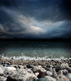 Sea stones waves and dark sky Stock Image