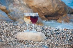 Sea stones and wineglasses on beach stock photos