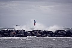 Sea Storm and American Flag. October 2015 Just north of Boston Ma. This flag was placed on these breakwaters after 9-11 and has been maintained ever since. And stock photography