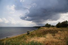 Sea and storm clouds. Storm clouds hung over the beautiful sea. Soon a shower, thunder and lightning will begin. Herbs in the meadow are crouched stock photography