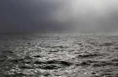 Sea storm in fog. With grey metallic lustre waves in foreground royalty free stock photo