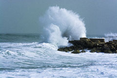 Sea storm waves crashing and splashing against jetty Stock Image