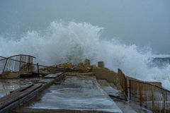 Sea storm waves crashing and splashing against jetty Stock Images