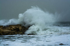Sea storm waves crashing and splashing against jetty Stock Photos