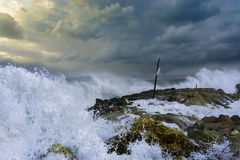 Sea storm waves dramatically crashing and splashing against rocks Royalty Free Stock Images
