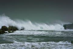 Sea storm waves dramatically crashing and splashing against rocks Royalty Free Stock Image