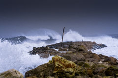 Sea storm waves dramatically crashing and splashing against rocks Stock Photos