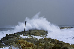 Sea storm waves dramatically crashing and splashing against rocks Royalty Free Stock Photos