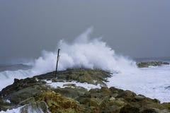 Sea storm waves dramatically crashing and splashing against rocks Royalty Free Stock Photos