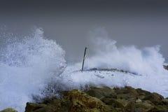 Sea storm waves dramatically crashing and splashing against rocks Royalty Free Stock Images