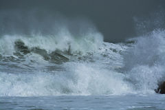 Sea storm waves dramatically crashing and splashing against rocks Royalty Free Stock Photo