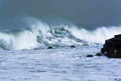 Sea storm waves dramatically crashing and splashing against rocks Stock Photos