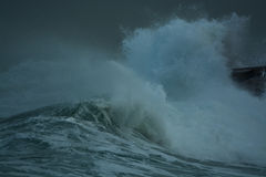 Sea storm waves dramatically crashing and splashing against rocks. Winter Sea storm with big rough and powerful waves crashing and splashing against a wet rocks royalty free stock photos