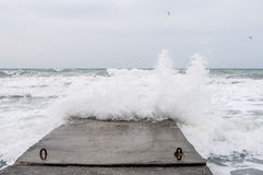 Sea strong storm waves crashing on stone pier Stock Photos