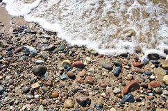 Sea summer beach sand background with stones and wave Stock Image
