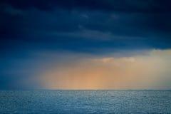 Sea. Sun beam through heavy sky over calm Stock Images