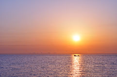 Sea at sunrise. City silhouette from sea at sunrise Royalty Free Stock Images