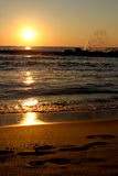Sea sunrise. With waves and footprints on sand Stock Image